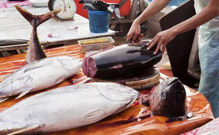 butchering: Butcher cutting tuna in a fish market in Asia