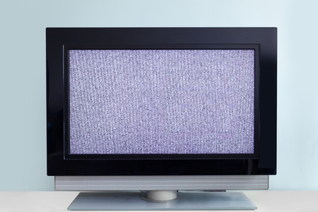 outage: Modern LCD TV with signal noise, against blue wall Stock Photo