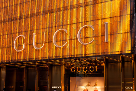 gucci store: Hong Kong, China - August 21, 2011: Sign of Gucci store at Canton Road, Tsim Sha Tsui, Hong Kong, illuminated at night. Gucci is an Italian fashion and leather goods brand, part of the Gucci Group.