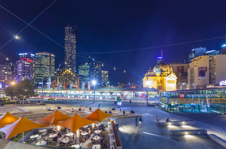federation: Melbourne, Australia - April 30, 2015: View of modern buildings and Flinders Street Railway Station in Melbourne, Australia at night