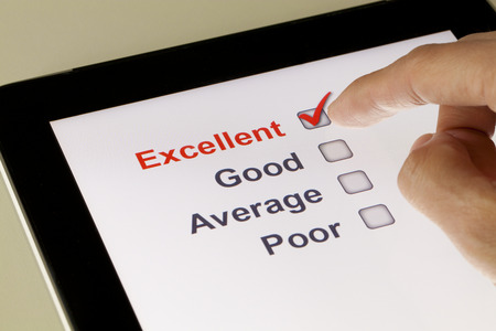 online survey: Completing online survey on a tablet, clicking excellent Stock Photo