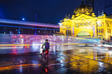 road cycling: Melbourne, Australia - May 14, 2015: View of a crossroad outside Flinders Street Railway Station in downtown Melbourne, Australia at night