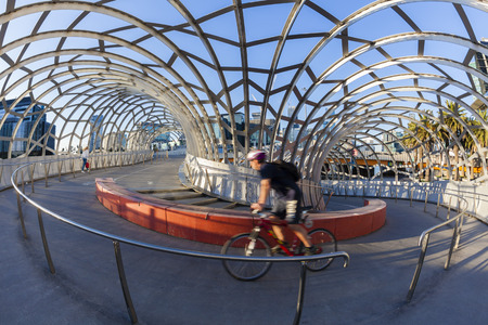 docklands: Melbourne, Australia - May 18, 2015: View of cyclist riding along the Webb Bridge in Docklands, Melbourne. Webb Bridge is a specially designed bridge over the Yarra River.