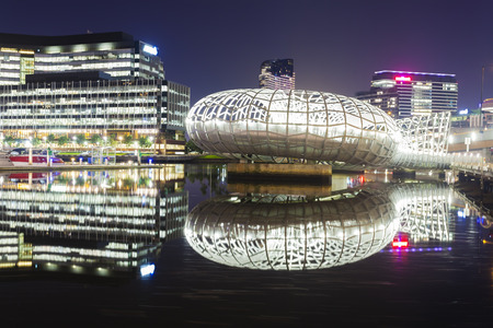 View of the Webb Bridge and modern buildings in Docklands, Melbourne at night. Webb Bridge is a specially designed bridge over the Yarra River.