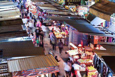 china people: Hong Kong, China - November 16, 2011: Street vendors and people shopping in Fa Yuen Street, MongKok, Hong Kong. The street is full of vendors selling exotic fruits, vegetables and bargain-priced clothing. Editorial