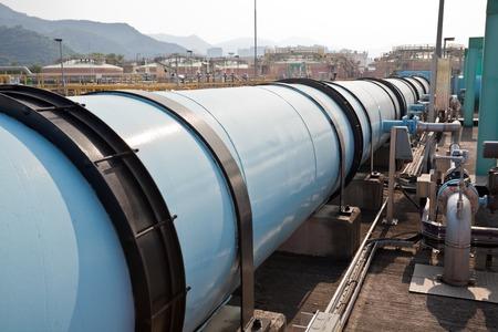 aguas residuales: Tubería de agua grande en una planta de tratamiento de aguas residuales con tanques de digestión en el fondo