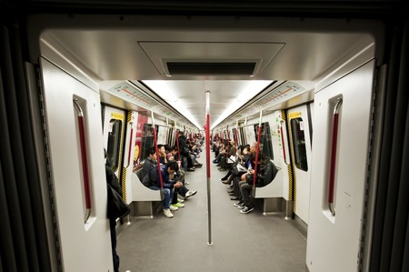 railway transportation: Hong Kong, China - January 1, 2011: Commuters inside a subway train in Hong Kong. The railyway, known as Mass Transit Railway, MTR, is the rapid transit railway system in Hong Kong. It is a common mode of public transport in Hong Kong.
