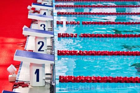nadando: Fila de parrilla de salida en una piscina