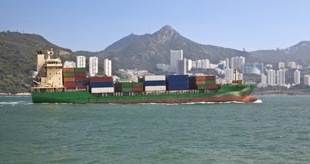 obchod: Cargo ship full of containers sailing across a harbour Reklamní fotografie