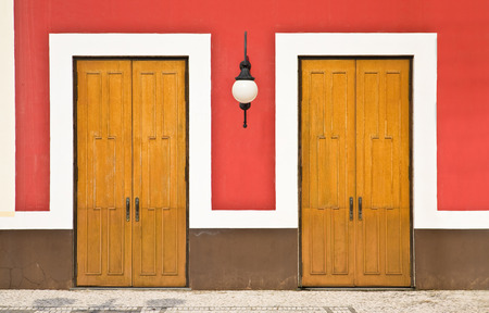 view of a wooden doorway: Front view of two doors against red wall Stock Photo