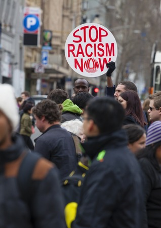 bigotry: Melbourne, Australia - Jul 25, 2015: Protester holding a stop racism now placard in the crowd outside Flinders Street Station in Melbourne, Australia Editorial