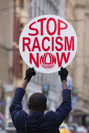 bigotry: Melbourne, Australia - Jul 25, 2015: Protester holding a stop racism now placard outside Flinders Street Station in Melbourne, Australia Editorial