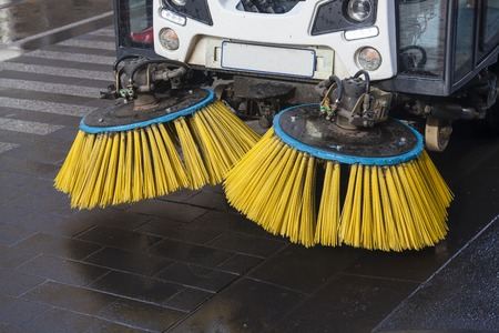 Close-up of the brushes of street sweeper