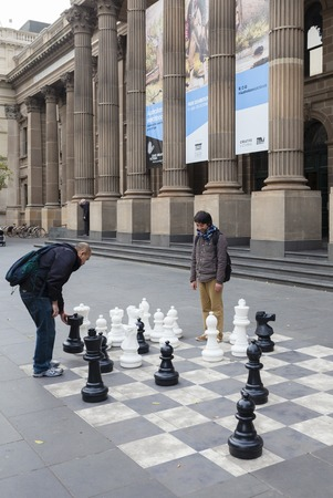 outdoor outside: Melbourne, Australia - Aug 1, 2015: Two mean playing outdoor chess outside the State Library of Victoria in Melbourne, Australia