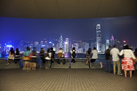 finanical: Hong Kong, China - October, 25th 2009: Tourists admiring the beautiful night view of the Victoria Harbour in Hong Kong