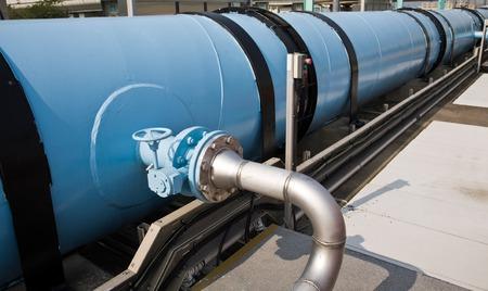 aguas residuales: Tubería de agua grande en una planta de tratamiento de aguas residuales, con tanques de digestión Foto de archivo