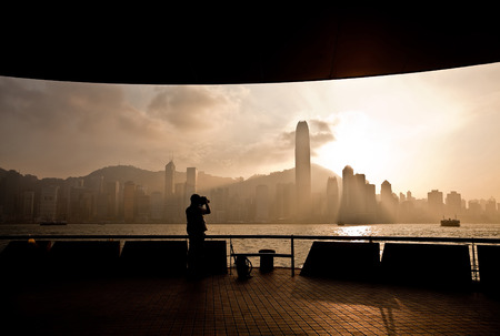 Victoria Harbor in Hong Kong at sunset with silhouette of a photographer