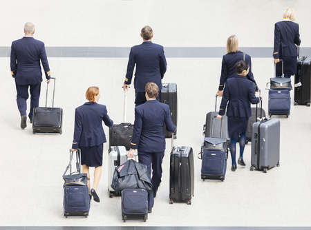 Hong Kong, China - June 12, 2015: Group of cabin crew walking at the Hong Kong International Airport, carrying their luggage