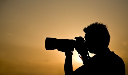 telephoto: Silhouette of a photographer holding a telephoto lens