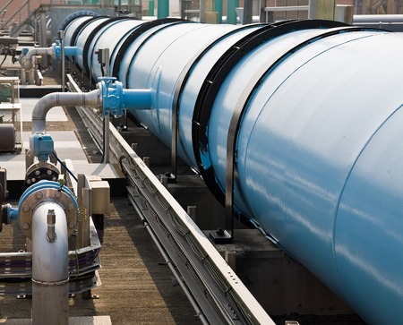 sewage treatment plant: Large water pipe in a sewage treatment plant, with digestion tanks in the background Stock Photo