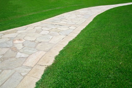 footpath: Cobble stone footpath on green grass field Stock Photo