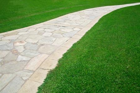 frontyard: Cobble stone footpath on green grass field Stock Photo
