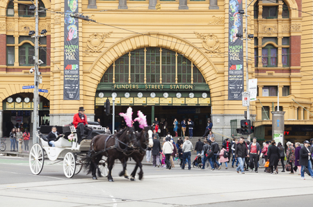 australia: Melbourne, Australia - Aug 29, 2015: People crossing a crosswalk outside Flinders Street Railway Station in Melbourne, Australia, with a horse-drawn carriage passing by
