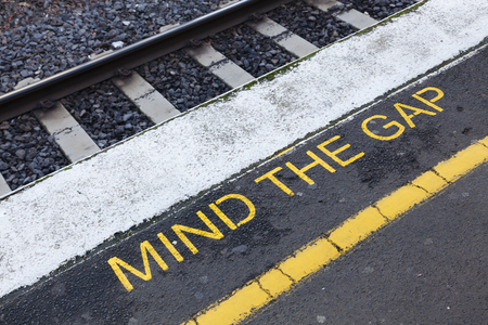 and danger: Mind the gap sign on a railway platform Stock Photo