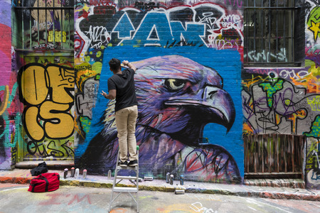 Melbourne, Australia - Sep 9, 2015: Street artist creating graffiti at Hosier Lane in Melbourne, Australia. Hosier Lane is a laneway in CBD of Melbourne, It is a popular landmark in Melbourne due to its graffitti covered walls and urban art. Imagens - 46768009