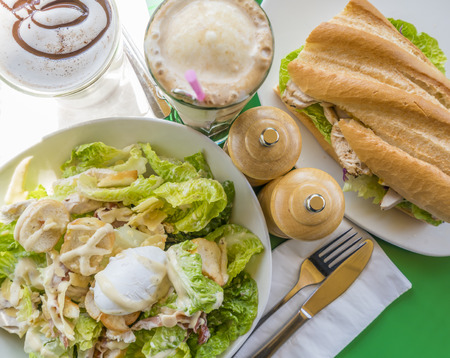 topdown: Top-down view of Caesar salad and chicken sandwich with chocolate drinks