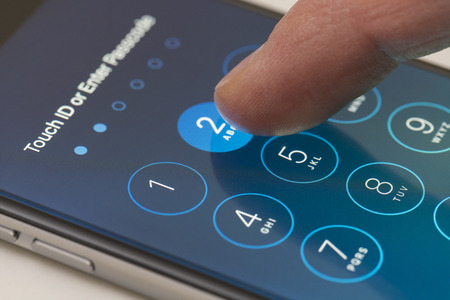 Melbourne, Australia - Sep 24, 2015: Entering passcode on an iPhone running iOS 9.  This new iOS release has six digits passcodes instead of four.
