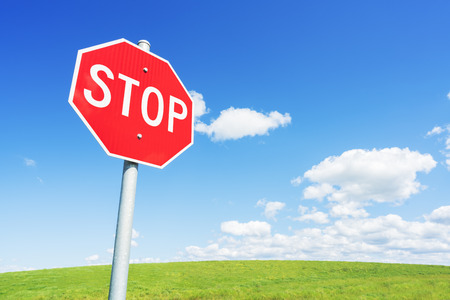 Stop road sign against blue sky and green field
