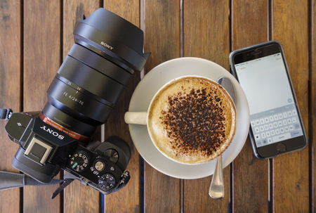 top down: Melbourne, Australia - Oct 1, 2015: Top down view of a cup of coffee , camera and an iPhone running the Notes app.