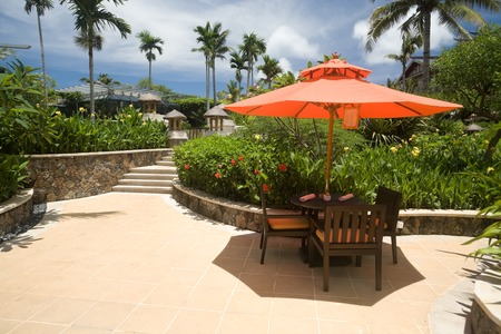 Outdoor chairs under sunshine in a tropical resort