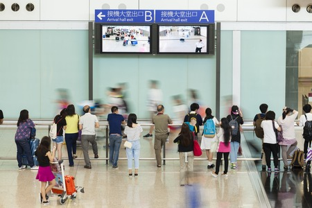 arrival: Hong Kong, China - June 12, 2015: People in the arrival hall of Hong Kong International Airport, waiting for their arriving friends and relatives Editorial