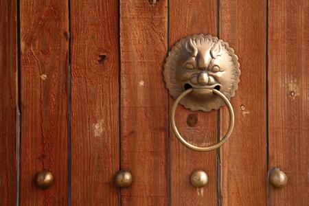 wood door: Close-up of chinese lion door knob on a wooden door