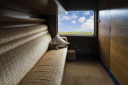 compartments: Travelling inside a luxurious vintage train carriage, window view with motion blur
