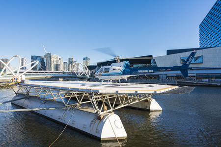 helipad: Melbourne, Australia - Nov 13, 2015: Helicopter landed on a floating helipad on Yarra River in Melbourne, ready to take passenger for a scenic tour over downtown Melbourne Editorial