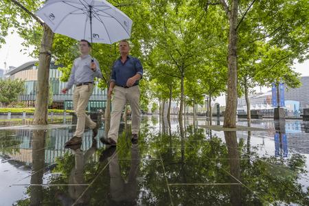 rain: Melbourne, Australia - Nov 10, 2015: Two men holding an umbrella walking in the rain in downtown Melbourne, Australia Editorial