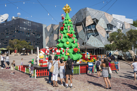 federation: Melbourne, Australia - Dec 16, 2015: People visiting the giant Christmas tree and Santa Claus made by Lego bricks on public display at Federation Square in Melbourne CBD