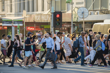 Melbourne, Australia - Dec 16, 2015: People walking across a busy crosswalk in downtown Melbourne at sunset