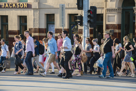 crowded street: Melbourne, Australia - Dec 16, 2015: People walking across a busy crosswalk in downtown Melbourne at sunset