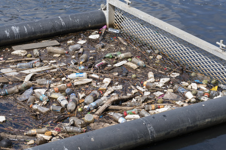 polluting: Melbourne, Australia - Jan 7, 2016: Litter trap with rubbish floating on Yarra River in Melbourne CBD. These traps are used to scoop rubbish from water at selected locations in Melbourne. Editorial