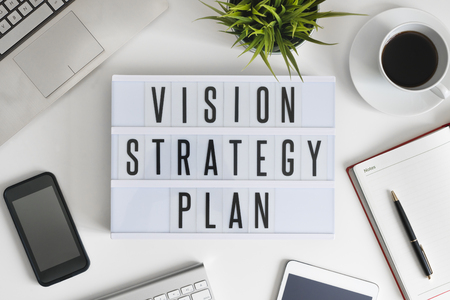 Vision, strategy and plan words on office table with computer, coffee, notepad, smartphone and digital tablet Stock Photo