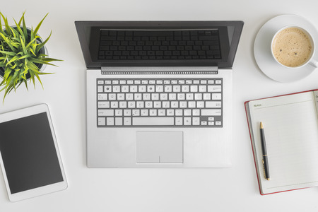 Flat lay photo of office desk with laptop, tablet, notebook and coffee