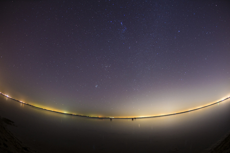 star sky: Starry night sky over clam water, with lights from a city in distant
