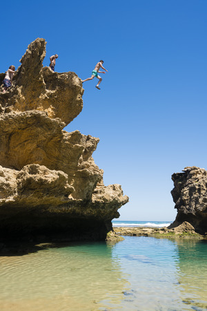 cliff jumping: Melbourne, Australia - Feb 6, 2016: People jumping off the Blairgowrie Jumping Rock into a rock pool in Bridgewater. It is a popular place for cliff jumping in Melbourne.