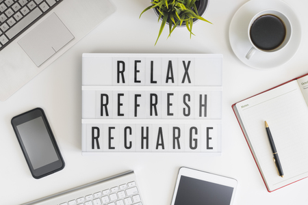 relax: Relax, refresh and recharge words on office table with computer, coffee, notepad, smartphone and digital tablet