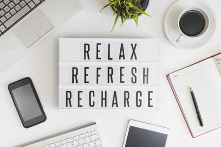 Rilassarsi, aggiornare e ricaricare le parole sul tavolo ufficio con computer, caffè, blocco note, smartphone e tablet digitale Archivio Fotografico