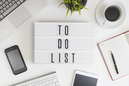 To do list words on office table with computer, coffee, notepad, smartphone and digital tablet